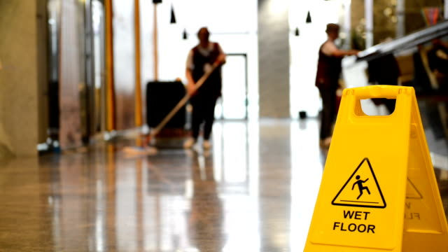 Sign showing warning of caution wet floor and workerw cleaning hall floor of  business building.