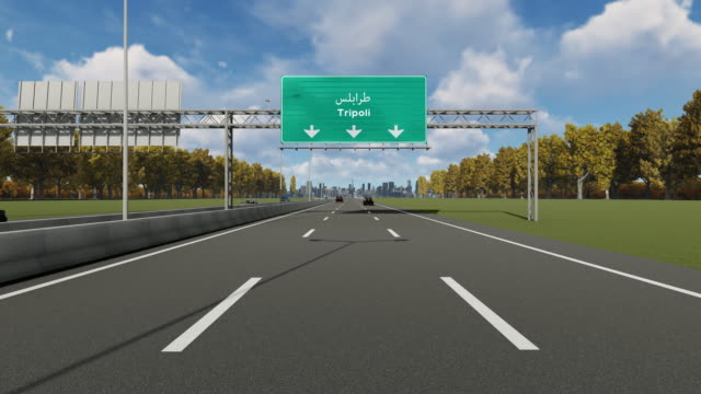 signboard on the highway indicating the entrance to tripoli city 4k stock video - libia video stock e b–roll