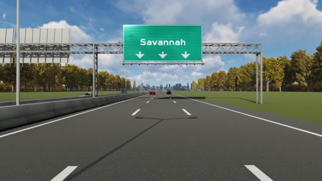 hinweis schild auf dem highway, der die einfahrt nach usa savannah city anzeigt - savanne stock-videos und b-roll-filmmaterial