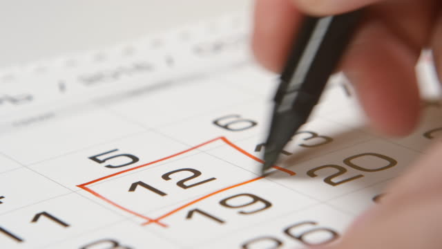 Signing a day on a calendar by red pen (square) video