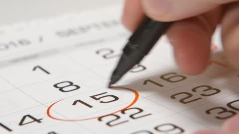 podpisywanie dnia w kalendarzu za pomocą czerwonego pióra - data filmów i materiałów b-roll