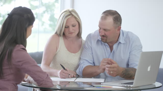Signing a Loan Agreement A financial advisor explains a loan agreement to a married couple. They sign it and shake hands. mortgages and loans stock videos & royalty-free footage