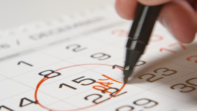 Signing a pay day on a calendar by red pen video
