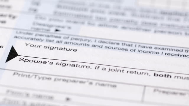 Signing a Tax Form A macro video clip of a woman's hand signing a tax form. taxes stock videos & royalty-free footage