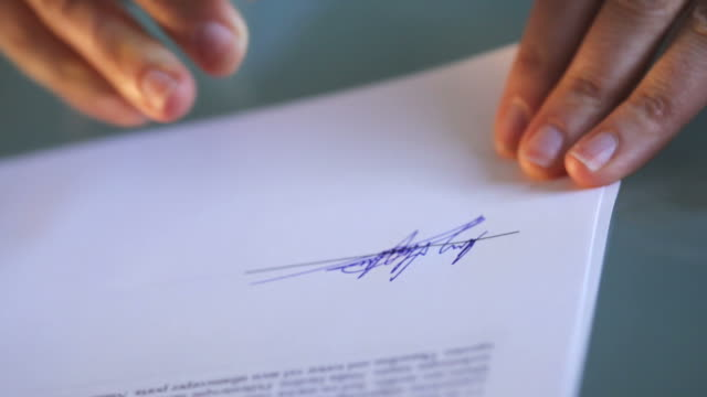 Signing_documents BS OF Close up of a woman's hand writing a signature with a fountain pen on the bottom of successive sheets of paper.  Canon 5D 100mm macro lens. contract stock videos & royalty-free footage