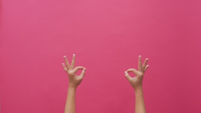 signs language hand isolated pink background 4k - perfezione video stock e b–roll