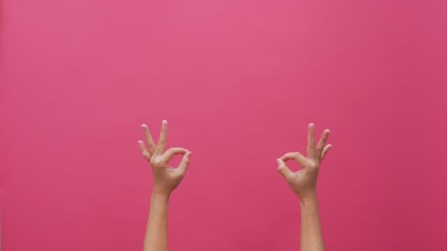 vidéos et rushes de langue des signes à la main fond rose isolé 4k - perfection