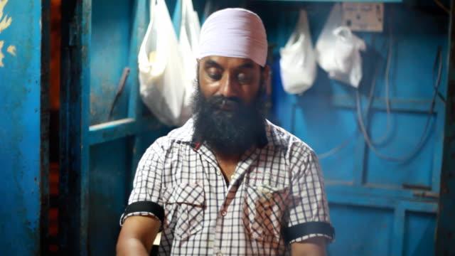 Sikh Man Preparing Assorted Barbequed Tandoori Chicken in Delhi India