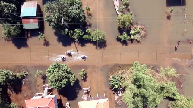 silder schot verticaal motoren rijden op overstroomde straat via een landelijk dorp video