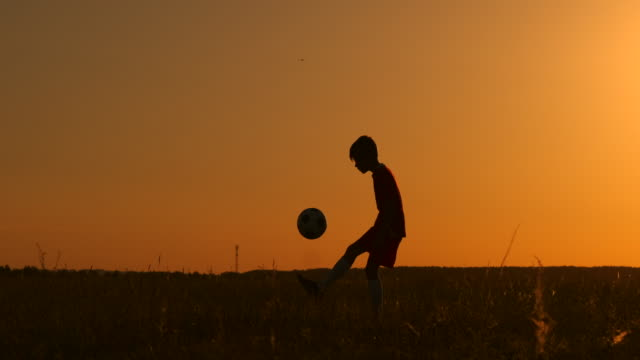 Silhouette a boy juggles a ball in the field at sunset.