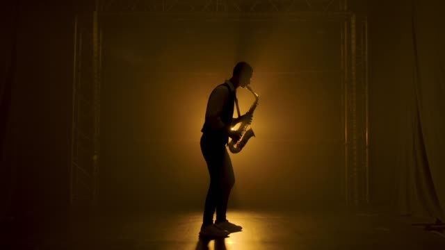 sylwetka młodego stylowego faceta gra złoty błyszczący saksofon w żółtych reflektorach na scenie. ciemne studio z dymem i neonowym oświetleniem. zespół wokalno-muzyczny. widok z boku. zwolnionym - podświetlony filmów i materiałów b-roll