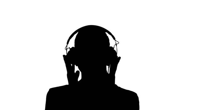 Silhouette A young woman listening to music in headphones