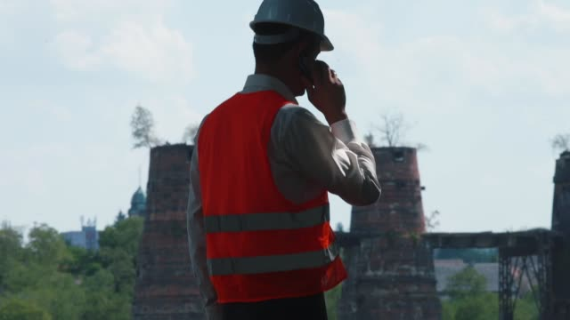Silhouette an engineer in helmet using phone. Transmission verbal messages Silhouette of an engineer in a helmet using the phone. Transmission of verbal messages at a distance using telecommunication. craftsman architecture stock videos & royalty-free footage