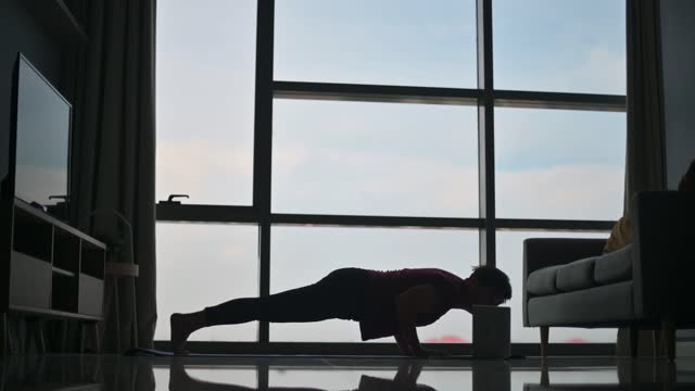 silhouette  asian chinese beautiful woman workout at home mediating on yoga mat at living room near the window on weekend morning