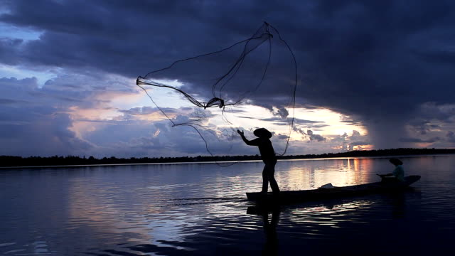 vídeos de stock e filmes b-roll de hd: silhouette asian fisherman on wooden boat casting a net for catching freshwater fish in nature river in the early morning before sunrise - fishman