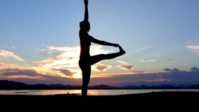 silhouette Asian women are exercising with yoga outside near the river in the evening. video