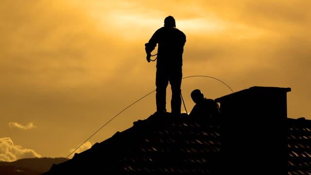 stockvideo's en b-roll-footage met silhouet bij zonsondergang maakt schoorsteen vegen en repari services - schoorsteen