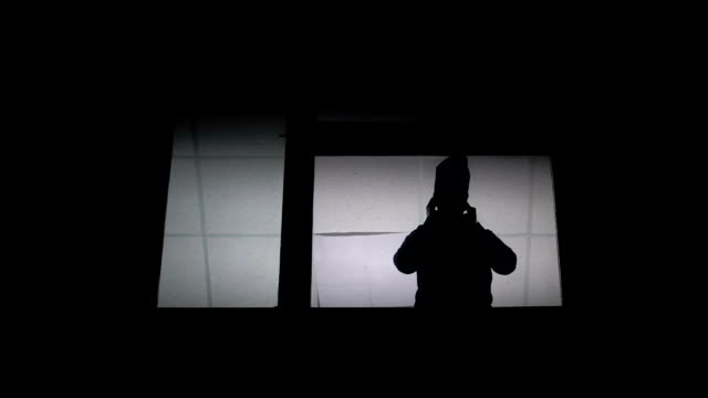 Silhouette at window putting on balaclava and leaving, getting ready for crime Silhouette at window putting on balaclava and leaving, getting ready for crime mask disguise stock videos & royalty-free footage