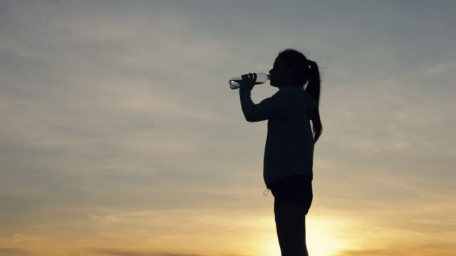 Silhouette athlete female runner drinking water after running fitness workout at the beach in the last sunlight. Healthcare lifestyle concept.
