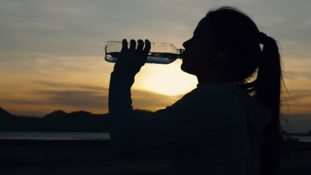 Silhouette athlete woman runner drinking water after running fitness workout at the beach in the last sunlight. fitness and healthy lifestyle concept. Slow Motion Shot.