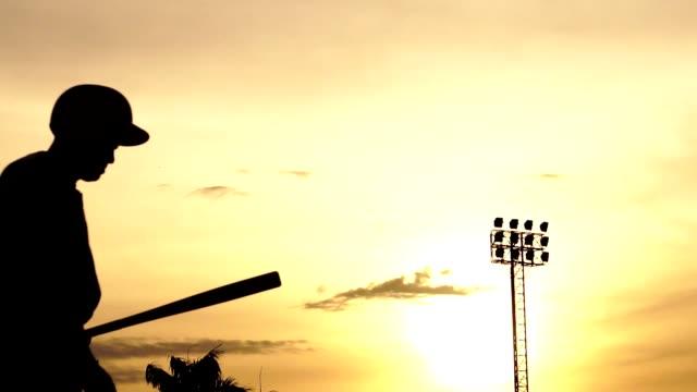 balo matkaplar vurmak için bir beyzbol sopası tutan siluet beyzbol oyuncusu - baseball stok videoları ve detay görüntü çekimi