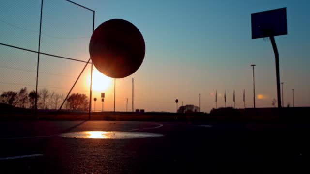 ms super slow motion silhuett basket studsar på utomhus basketplan vid solnedgången - basketboll boll bildbanksvideor och videomaterial från bakom kulisserna
