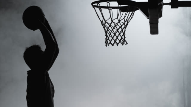 SLO MO of silhouette basketball player dunking the ball video