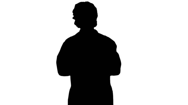 Silhouette Beautiful doctor is talking while walking Medium shot. Silhouette Beautiful doctor is talking while walking. Professional shot in 4K resolution. 006. You can use it e.g. in your commercial video, business, presentation, broadcast eye chart stock videos & royalty-free footage