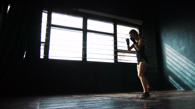 silhouette beautiful young boxing woman training punching in fitness studio slow motion