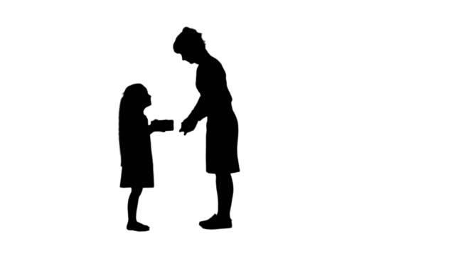 Silhouet mooie jonge mama een cadeautje geven aan haar charmante meisje bijhouden mat video