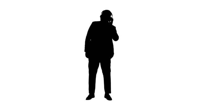 Silhouette Black businessman dancing to music in headphones