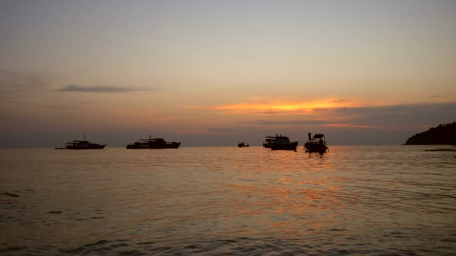 silhouette boats with golden sunset in a sea - crostaceo video stock e b–roll