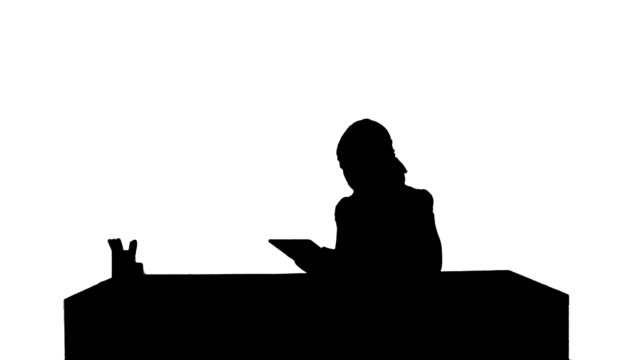 Silhouette Business woman sitting in her office using a tablet computer video