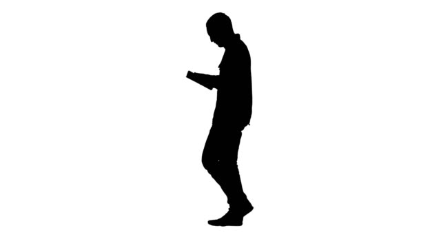 Silhouette Confident serious man walking and working in tablet Full length portrait side view. Silhouette Confident serious man walking and working in tablet. Professional shot in 4K resolution. 004. You can use it e.g. in your commercial video, business, presentation, broadcast silhouette people stock videos & royalty-free footage