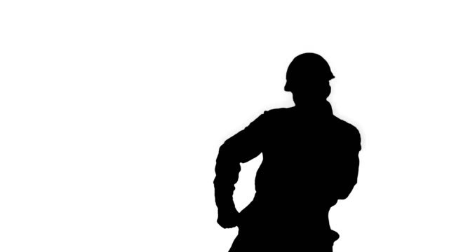 Silhouette Construction worker in helmet dancing Medium shot. Back view. Silhouette Construction worker in helmet dancing. Professional shot in 4K resolution. 022. You can use it e.g. in your commercial video, business, presentation, broadcast craftsman architecture stock videos & royalty-free footage
