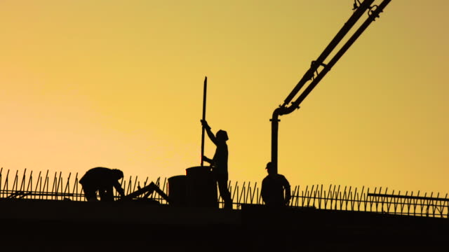 Silhouette construction working in construction site during sunset