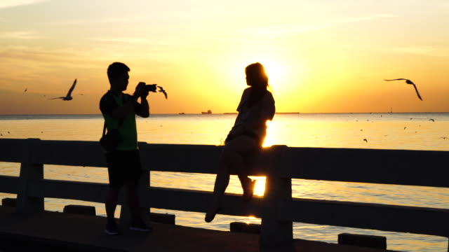Silhouette couple take a photograph with seagulls while sunset at Bang Pu, Thailand