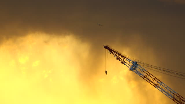 Silhouette Crane in building construction site on Sunset Background Silhouette Crane in building construction site on Sunset Background construction machinery stock videos & royalty-free footage