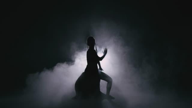 vídeos de stock, filmes e b-roll de mulher do dançarino da silhueta que executa figuras da dança na névoa 4k imagens em câmera lenta. - arte, cultura e espetáculo
