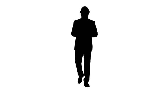 Silhouette Engineer in suit and helmet walking and writing notes in notepad