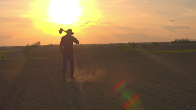 MS Silhouette farmer carrying hoe in idyllic,rural plowed field at sunset
