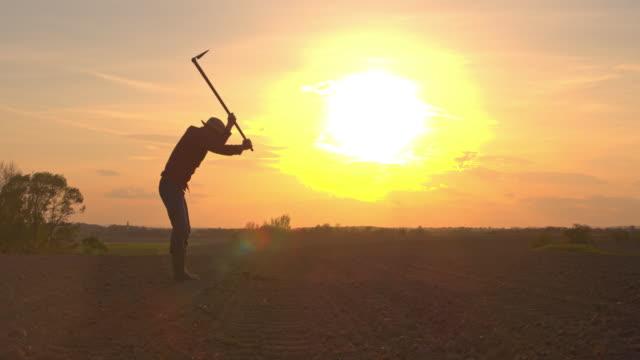 vídeos de stock, filmes e b-roll de agricultor de ms silhouette usando enxada no campo arado rural - terra cultivada