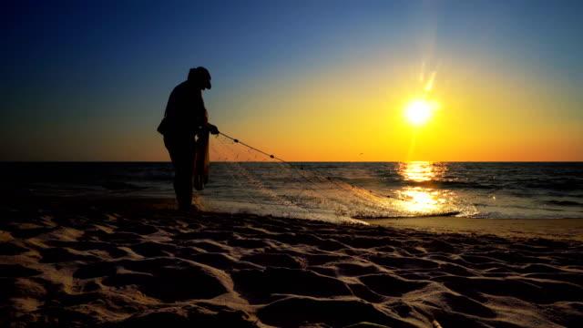 silhouette fischer fischernetz am sonnenuntergang strand; kinofsteadicam erschossen - fang stock-videos und b-roll-filmmaterial