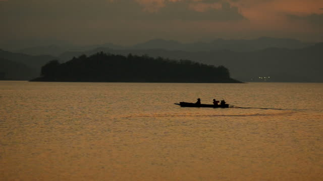 silhouette : fishers are coming to home on long boat in dam at twlight
