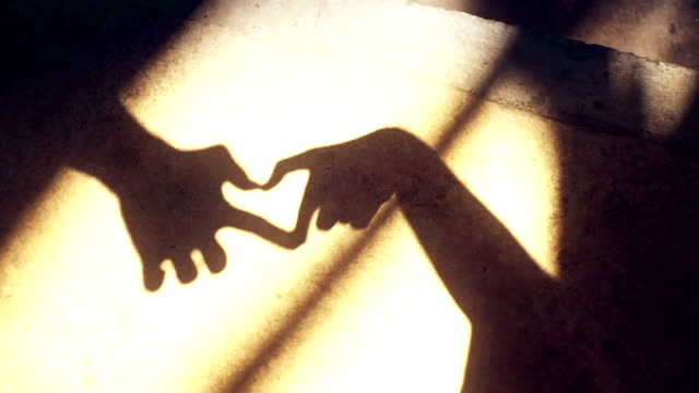 Silhouette forming heart shape shadow by hands on the ground for Valentine's day.