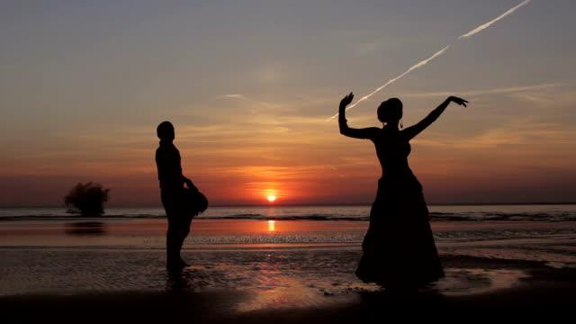 stockvideo's en b-roll-footage met silhouet meisje dansen exotische dans met drummer - oost aziatische cultuur