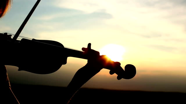Silhouette girl violinist playing the violin at sunset. Close up.