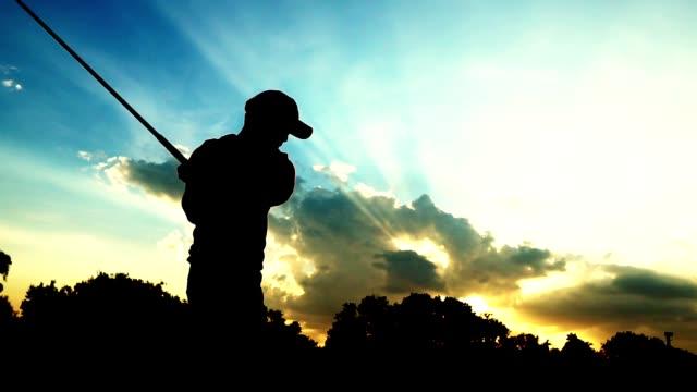 silhouette golfer mann mit dunklen licht des sonnenuntergangs - golf stock-videos und b-roll-filmmaterial