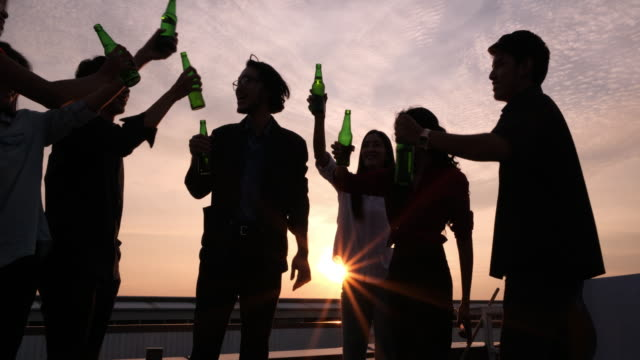 silhouette group of friends enjoying party and throwing confetti. friends having fun at rooftop party.group of friends at club having fun. new year's party - terrazza video stock e b–roll