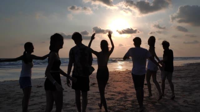 silhouette group of friends having fun on the beach.happy smiling friends walking seaside sea ocean holiday travel.vacations - istock - podświetlony filmów i materiałów b-roll